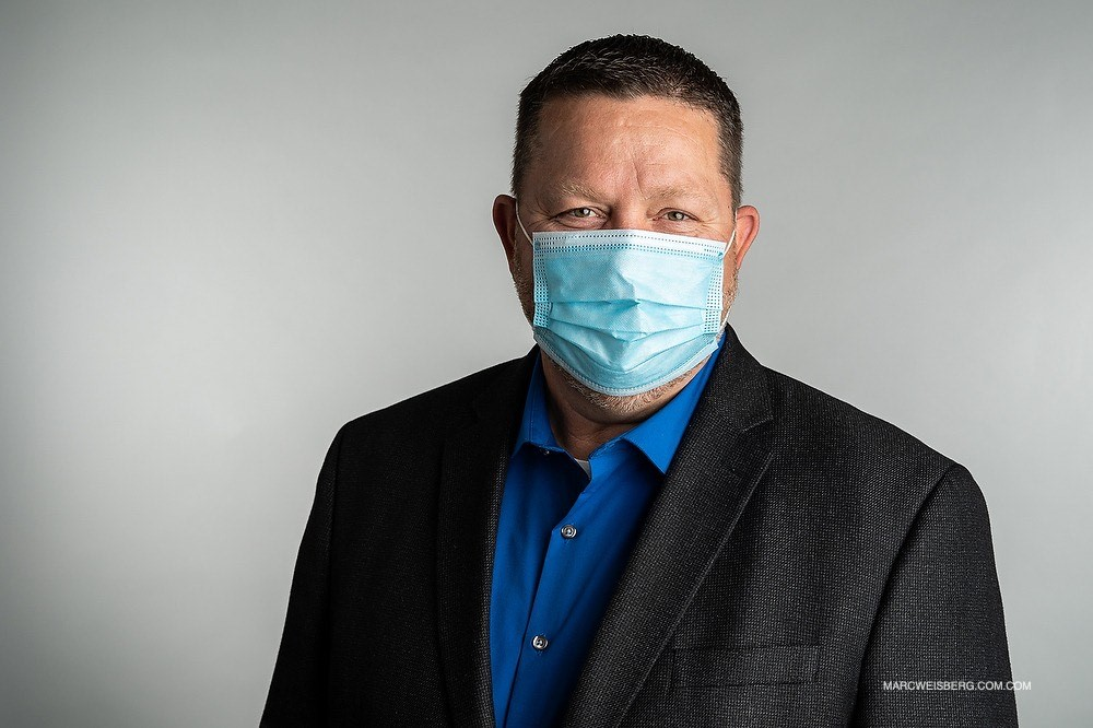 Portrait of Bill Mazurek wearing a medical mask