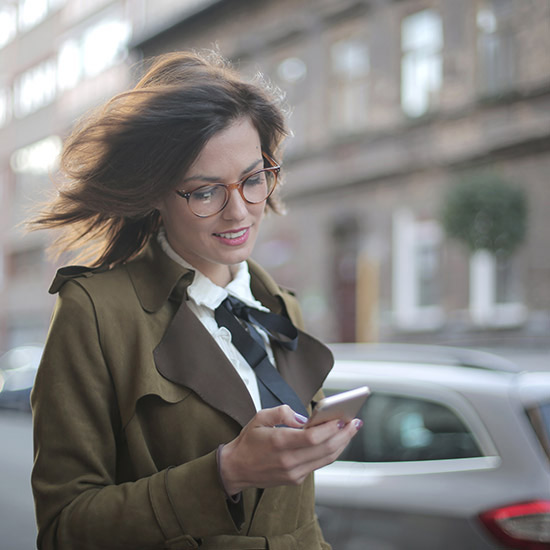 smiling business woman looking at cell phone